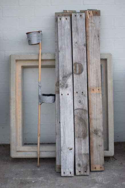 Drink holder stored against wall with wood planks